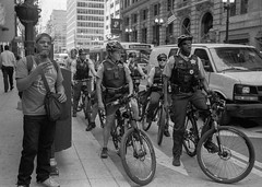 Chicago Police Bicycling In The Summer Heat. (Jovan Jimenez) Tags: canon eos rebel t2 ef 40mm stm f28 kodak tmax 3200 police cop bike people chicago bicycling city street black white gray bw monochrome monochromatic film analog analogue grain summer heat streetphotography