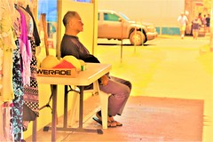 Sitting (thomasgorman1) Tags: man store storefront sitting sidewalk street streetscens streetphotos faded sepia processed nikon outdoors downtown hawaii candid molokai island cane table clothes people retail shopping