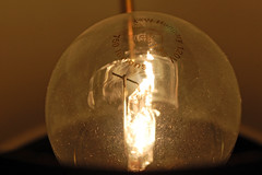 Illuminated Light Bulb. (dccradio) Tags: lumberton nc northcarolina robesoncounty indoor indoors inside light filament illuminate illuminated lamp lightbulb bulb glass words text ge generalelectric hungary 43w 120volt 750 lit shade lampshade night nikon d40 dslr dust dusty
