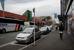Outside the Bus Station (Jocey K) Tags: newzealand nikond750 christchurch cbd building architecture people street road coaches bues flags cars sky