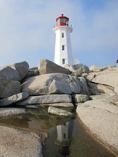 Puddle amid granite reflects the lighthouse, Peggy's Cove, Nova Scotia