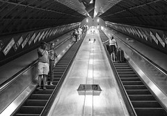 Thats Heavy Luggage (tcees) Tags: londonbridge undergroundstn london se1 londontransport escalator tube people man woman handrail adverts arch lights urban roof ceiling suitcase x100 fujifilm finepix streetphotography street bw mono monochrome blackandwhite