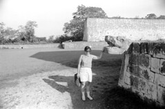 071470 21 (ndpa / s. lundeen, archivist) Tags: nick dewolf nickdewolf july blackwhite photographbynickdewolf bw 1970 1970s monochrome blackandwhite film mexico mexican yucatán yucatan yucatanpeninsula chichénitzá chichenitza ancient ruins city mayan ancientmayancity greatballcourt ballcourt complex greatballcourtcomplex wall stone stones woman brunette sunglasses shades bag shoulderbag shorts carving stonecarving animal animalhead