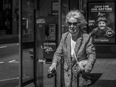 Age-Defying (Leanne Boulton) Tags: portrait urban street candid portraiture streetphotography candidstreetphotography candidportrait streetportrait streetlife old elderly woman age female face sunglasses windswept wind windy weather walkingframe mobility juxtaposition sign tone texture detail depthoffield bokeh naturallight outdoor light shade shadow sunlight city scene human life living humanity society culture people canon canon5d 5dmkiii 70mm ef2470mmf28liiusm black white blackwhite bw mono blackandwhite monochrome glasgow scotland uk