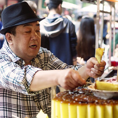Man buying cake in the Muslim Quarter, Xian (BryonLippincott) Tags: muslimmarket xian china asia asian chinese market portrait en environmentalportrait muslim muslimquarter tourism tourist travel destination street man vendor shopkeeper eyes focused hat islam islamic cake food streetfood