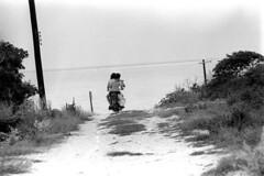 073270 02 (ndpa / s. lundeen, archivist) Tags: nick dewolf nickdewolf july blackwhite photographbynickdewolf bw 1970 1970s monochrome blackandwhite film mexico mexican yucatán yucatan yucatanpeninsula islamujeres island caribbean yamaha motorcycle motorbike woman maggie child boy motherandson alexander road dirtroad ocean sea utilitypoles powerlines