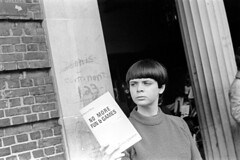 040870 14 (ndpa / s. lundeen, archivist) Tags: nick dewolf nickdewolf blackwhite photographbynickdewolf bw 1970 1970s 35mm film monochrome blackandwhite april cambridge massachusetts mass harvardsquare people woman youngwoman brunette bangs shorthair sweater publication book booklet feminist activist literature nomorefungames journal thedialecticsofsexism ajournaloffemaleliberation femaleliberationfront issuethree issue3 building graffiti brickbuilding column pillar cell16 militantfeminist newspaper timesup womensmovement