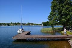 Lithuania / Trakai / Boat Dock (Pantchoa) Tags: lituanie trakai lac eau voilier embarcadère personne arbres bateau cielbleu joncs casquette rivage