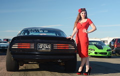 Holly_9163 (Fast an' Bulbous) Tags: classic american muscle car vehicle automobile fast speed power pinup model girl woman wife hot sexy chick babe red wiggle dress high heels long brunette hair stockings nylons people outdoor sky