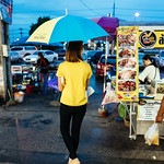 Yellow shirt, yellow and blue umbrella. thumbnail