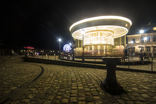 night view of the spinning merry-go-round (carousel / manage) and turning ferris wheel (grande roue) in full glow, fine art, Honfleur, Calvados, Normandy, France