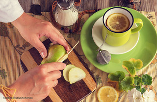 Hands are cutting a pear. Next tea with lemon in a green cup, sugar bowl, a board with a green pear and a knife. Atmospheric photo. Fresh bright colors. Top view.