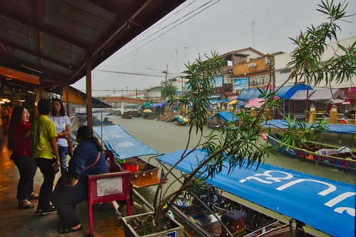 Heavy rain shower at Amphawa floating market in Samut Songkhram province near Bangkok, Thailand