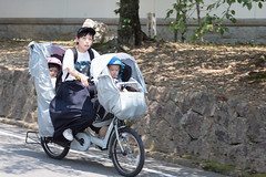 Mother and toddlers on a lowrider E-bike, Kyoto, Japan (mistermacrophotos) Tags: bicycle electric covered up children cute plastic low bike transportation commute school run helmets bikke summer wrapped blue family street scene green energy hat woman cool three different expressions boss booswoman mother mum mom moped