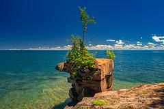 Madeline Island shoreline (susannevonschroeder) Tags: lakesuperior wisconsin blue clouds landscape rocks sky summer trees apostleislands statepark bigbay