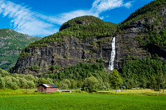 Vassbakkfossen Waterfall and Mountain Farm (briburt) Tags: briburt fuji fujifilm fujinon xe1 xf1855 mountains sun water glacial vassbakkfossen vassbakkwaterfall waterfall summer light farm norway field green grass bridge norwegian blue glow sky azure panorama landscape dramatic contrast majestic rugged stark lake skjolden fortun vassbakken mountain tree forest woods wood stone cliff sognogfjordane
