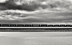 Train on the Utah Salt Flats (rolfstumpf) Tags: usa utah saltlake greatsaltlake saltflats unionpacific westernpacific interstate80 trains railway railroad monochrome bnw blackandwhite freightcar olympus sky clouds silhouette