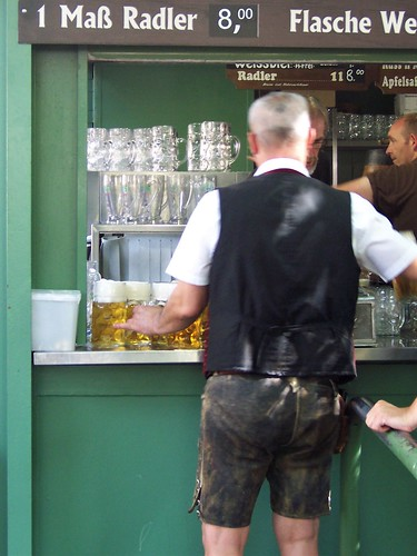 Waiter in lederhosen loading up with giant beers