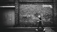 Heading in the right direction. (Mister G.C.) Tags: street urban photography blackandwhite bw olympus xa2 olympusxa2 dzuiko zuikolens f35 35mm primelens fullframe compactcamera compact camera zone focus zonefocusing streetphotography urbanphotography shot image photograph people unposed man male guy brickwall wall graffiti arrow direction gritty fullstride monochrome town city analog analogphotography analogue film filmcamera schwarzweiss strassenfotografie mistergc niedersachsen lowersaxony germany europe