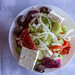 Top view of traditional Greek salad with peppers, cucumbers, onions, olives and feta cheese