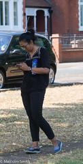 Modern Communication 24 (M C Smith) Tags: pentax k3ii walking phone woman parking black wall pavement tree grass path blue white silver shadows reflections railings bricks