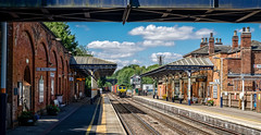 Melton in sunshine (Peter Leigh50) Tags: shed shadows station train railway railroad rail freightliner freight containers melton mowbray building people class 66 sky clouds sunshine fujifilm fuji xt10