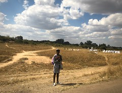 Boy crossing the highway (The Advocacy Project) Tags: africa zimbabwe harare boy road grass highway paths landscape sky clouds backpack