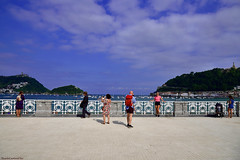 Posando con fondo - Posing with background (ricardocarmonafdez) Tags: donostia sansebastian streetphotography people cielo sky nubes clouds sunlight nikon d850 24120f4gvr