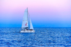 Sailing at pink o'clock (Fnikos) Tags: sea water seascape serene blue sky skyline pink boat sailboat people outdoor