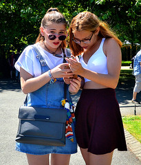 Distracted (Owen J Fitzpatrick) Tags: ojf people photography nikon fitzpatrick owen pretty pavement chasing d3100 ireland editorial use only ojfitzpatrick eire dublin republic city tamron candid joe candidphotography candidphoto unposed natural attractive beauty beautiful woman female lady j face along photoshoot street 2018 streetphoto st saint stephens green area colour colourful device phone handset digital skirt shades sunglasses bag parkland denim hold eye contact distracted glasses handbag park