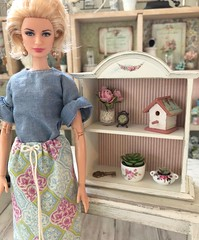 Today I tried to make a gathered skirt. I ended up using a drawstring because it was easier. I also finished up this little shelf today. I salvaged it from broken 1/12 scale dollhouse furniture. I wish I enjoyed redoing life-size furniture as much as I do (JunqueDollBoutique) Tags: grace kelly barbie purse junque doll boutique store shop buy shabby chic cottage french country farmhouse dio diorama 16 one sixth scale room house dining shelf display home decorations decor accessories birdhouse plant succulent pink roses