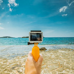 Man holding underwater camera (like GoPro) at the beach thumbnail