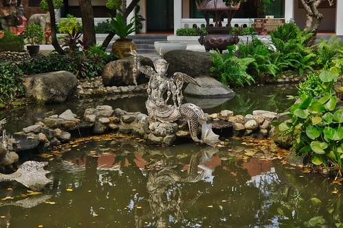 Pond and sculpture int the garden of Erawan museum in Samut Phrakan province near Bangkok, Thailand