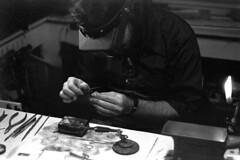 010971 13 (ndpa / s. lundeen, archivist) Tags: nick dewolf nickdewolf blackwhite blackandwhite 35mm film photographbynickdewolf bw january 1971 1970s boston massachusetts beaconhill charlesstreetmeetinghouse meetinghouse gallery meetinghousegallery metalsmith jewelrymaker workspace pipe pipesmoker pipesmoking metalsmithing makingjewelry man facialhair beard protectiveglasses watch wristwatch table worktable desk tools equipment ring flame torch magnifyingglasses jewelersglasses loupe jewelersloupe headband