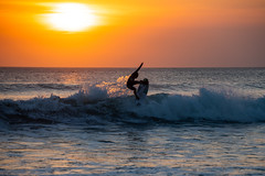A surfer under the setting sun (Masa_N) Tags: sun summer water people surfing bali kuta surfer wave sport evening outdoors indonesia orangecolor sea インドネシア id