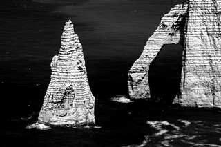 fine art black and white, dark water and striped rock of Porte d'Aval and L'Aiguille d'Etretat, the natural arch and needle just south of Etretat, Seine-Maritime, Normandy, France