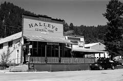 Halleys of Keystone (Harald Philipp) Tags: storefront saloon building structure sidewalk pavement village town street outdoors rural historic scenic patio deck window roof car road mountain hill vacation tourism tourist travel adventure wanderlust blackandwhite bw blackwhite monochrome schwarzweiss nocolor dark shadows contrast ilford delta400 35mm film grain analog filmphotography primelens kodakretina retinaiiic classiccamera rangefinder antiquecamera foldingcamera sky day unitedstates northamerica usa park nationalpark western westernusa southdakota keystone mtrushmore blackhills gold goldmining miningtown generalstore