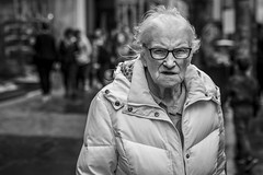 The Autumnal Summer Day (Leanne Boulton) Tags: portrait people urban street candid portraiture streetphotography candidstreetphotography candidportrait streetportrait eyecontact candideyecontact streetlife old elderly woman female lady face eyes expression glasses mood feeling emotion wet weather wind windy rain tone texture detail depthoffield bokeh naturallight outdoor light shade city scene human life living humanity society culture lifestyle canon canon5dmkiii 70mm ef2470mmf28liiusm black white blackwhite bw mono blackandwhite monochrome glasgow scotland uk