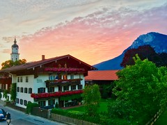 Sunrise over Kiefersfelden and Kaiser mountains in Bavaria, Germany (UweBKK (α 77 on )) Tags: dawn sun sunrise sky fire orange clouds church building architecture trees kaiser mountains kiefersfelden morning bavaria bayern deutschland germany europe europa iphone