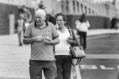 The ice cream eaters (Frank Fullard) Tags: frankfullard fullard candid street portrait couple pair icecream desert portrush ireland northernireland hiolidaymakers dayrtipper resort monochrome blackandwhite antrim coast seaside cool