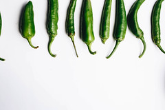 Top view of green chili peppers on white background. Details (wuestenigel) Tags: spice heat color sweet line space chilli healthy hot plant food macro spicy seasoning pile peppers ripe isolated paprika white vegetable eating chili detail red pepperoni fresh chile indian green ingredient pepper jalapeno studio freshness object vitamin cayenne background culture organic
