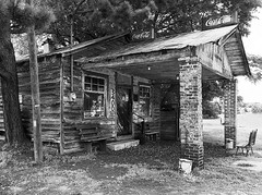 Sit a Spell and Have a Beer (Jon Meyer Photographic Art) Tags: store jonmeyer jonmeyerphotographicart jonmeyerphotography hasselblad monochrome blackandwhite columns tree pole buckets sign beer coke cocacola bench smalltown unitedstates northcarolina