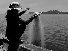 Fisherwoman (Janka Takács Sipos) Tags: bystander calle candid documentary flâneur photo photography public rue space stranger streetphoto streetphotographer unposed fish water fisherman fisherwoman boat sea bay halongbay vietnam asia rock net hat woman fishingnet island waves bnw black white blackandwhite monochrome fuji fujifilm x20 xseries