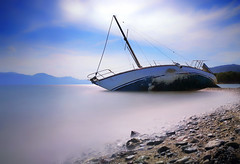 The Failure Of A Captain (Bo.Th) Tags: greece light landscape clouds blue silence calm relax colors beach boat abandoned quiet water waves seaside sea seascape dreaming rocks rock sky sun outdoor view coast mountain forgotten shipwreck