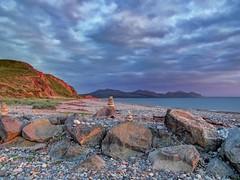 Sunset at Dinas Dinlle (Ian Gedge) Tags: uk britain wales northwales dinasdinlle sea seaside beach stones rocks pebbles shore sunset cymru sky mountains