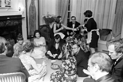 040271 20 (ndpa / s. lundeen, archivist) Tags: nick dewolf nickdewolf blackwhite monochrome blackandwhite 35mm film photographbynickdewolf bw 1971 1970s boston massachusetts social socializing party formal blacktie blacktieaffair people livingroom furniture windows curtains drapes woman women sittingonthefloor seated sitting floor onthefloor man men suit suits tie bowtie dress dresses food plates sudieschenck connaughtmahony coffeecups chair couch sofa glasses eyeglasses maid maidsoutfit fireplace mantle sideburns may