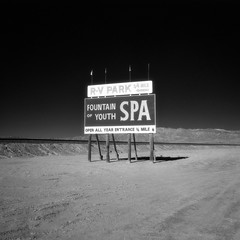 fountain of youth (infrared). bombay beach, ca. 2016. (eyetwist) Tags: eyetwistkevinballuff eyetwist fountainofyouth billboard sign bombaybeach saltonsea desert california mamiya 6mf 50mm kodak infrared ir hie 400 bw black white mamiya6mf mamiya50mmf4l kodakhighspeedinfraredhie ishootfilm ishootkodak analog analogue film square 6x6 mediumformat 120 filmexif filter bw091 deepred red 29 091 iconla aerial recon epsonv750pro lenstagger sonorandesert bleak americantypologies landscape roadsideamerica americana type typography lettering painted americanwest imperialcounty spa empty ca111 desolate barren sand chocolatemountains rvpark openallyear entrance arrow minimalism void vast blacksky