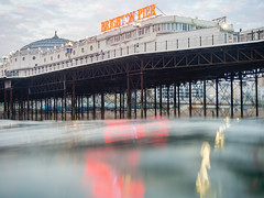 Brighton Place Pier from the water at Dusk (lomokev) Tags: green file:name=180712omdem57120070 olympusomdem5 olympus omd em5 olympusomd dof depthoffield focus reflection water brighton pier brightonpier palacepier red sign dusk wildswimming