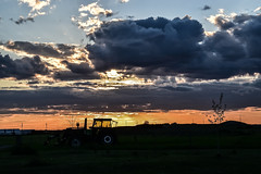 The day is done 4 (darletts56) Tags: sky blue sun sunset bright yellow glow cloud clouds thunder rain tree trees tracter silhouette grass green field fields prairie building buildings pole poles post posts light lamp agriculture street road hill tire tires storm stormy gold golden orange