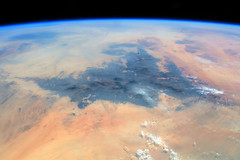 Mountains in the Sahara Desert (sjrankin) Tags: 21july2018 edited nasa iss iss056 iss056e95105 earthslimb africa saharadesert sand arid sanddunes mountains rockymountains rocky clouds